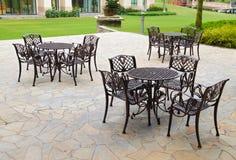 Vectores y sillas en el suelo de la piedra arenisca en el jardín Fotografía de archivo