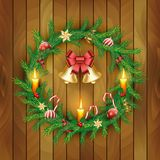 Vectorkerstmiskroon met gouden klokken, rode bessen, kaars, suikergoedriet, boog, ballen op houten raadsachtergrond royalty-vrije illustratie