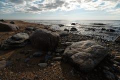 Veczemju Klintis -巨石城海滩在波儿地克的国家拉脱维亚在2019年4月-与愚钝的云彩和一点太阳的多云天 免版税库存照片