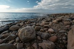Veczemju Klintis - Boulder beach in Baltic country Latvia in April 2019 - Cloudy sky with dull clouds and a bit of sun royalty free stock photos