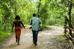 Vedda man in Dabana walks with tour guide royalty free stock photography