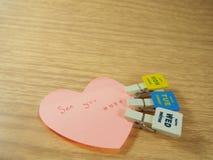 Vedivi sul Post-it, la forma del cuore, graffette Fotografie Stock Libere da Diritti