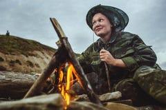 Vedträ för flickafotvandrareuppståndelser och se avlägset runt om lägereld på flodkust på aftonen Royaltyfri Fotografi