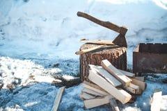 Vedträ och yxa nära grillfesten vinter för snow för pojkeferielay Royaltyfri Foto