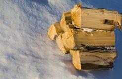 Vedträ som läggas trevligt ut på den vita snön Arkivbild