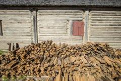 Vedträ som staplas upp lantligt hem för yttersida arkivfoton
