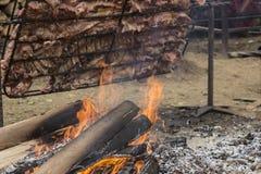Vedträbränning för att göra till kok griskött Arkivfoton