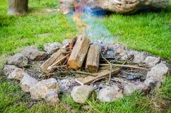 Vedträbränning i brand med rök som omges av stenar Royaltyfri Bild