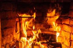 Vedträbränning i brandbrännskador i spisen Tegelstenugnen ger värme och värme från de brända journalerna Brännande kol och flammo royaltyfri fotografi