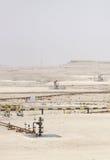 Veduta d'insieme della testa di pozzo dell'olio & delle pompe di olio in vasto affioramento del giacimento di petrolio del Bahrain Fotografie Stock Libere da Diritti