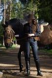 Veedrijfster die in hoed haar paard koestert stock foto
