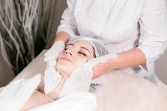Veeg met steriel servetgezicht af Jonge mooie vrouw die behandelingen in schoonheidssalons ontvangen Het gezichts het reinigen sc royalty-vrije stock afbeelding