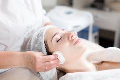 Veeg met steriel servetgezicht af Jonge mooie vrouw die behandelingen in schoonheidssalons ontvangen Het gezichts het reinigen sc stock afbeelding
