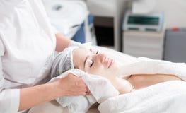 Veeg met steriel servetgezicht af Jonge mooie vrouw die behandelingen in schoonheidssalons ontvangen Het gezichts het reinigen sc stock foto