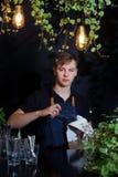 Veegt het de schort jonge glas van de barmankelner fouger de zwarte flitslichten die van achtergrondkoffiebladeren licht ontwerp  royalty-vrije stock foto