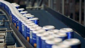 Veel blikken met bier op een fabriekstransportband, sluiten omhoog stock footage