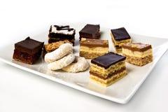 Veel cakes en koekjes op een geïsoleerdeb plaat Stock Afbeelding