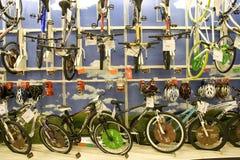 Veel fietsen en helmen voor verkoop in opslag stock foto