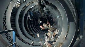 Veel huishoudelijk afval die in een machine om te recycleren worden gesorteerd stock videobeelden