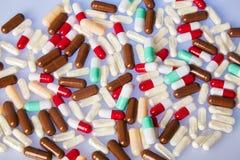 Veel kleurrijke drugs en pillen op blauwe spiegelachtergrond stock foto's