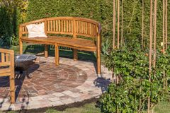 Veel liefs ontworpen tuin met steencirkel, houten banken en brandkom stock afbeeldingen