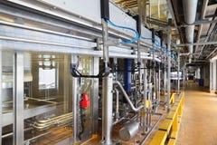 Veel pijpen en reservoirs bij grote fabriek Stock Foto