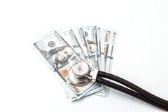 Veel rekeningen van 100 dollars en stethoscoop, Amerikaans bankbiljet, groene achtergrond met het close-up van de contant geldmun Stock Fotografie