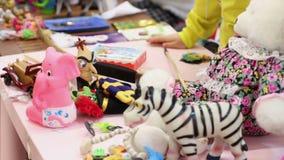 Veel speelgoed die op lijst, kinderen liggen die spelen spelen bij kleuterschool of weeshuis stock video
