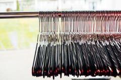 Veel verscheidene hangers van de metaaldraad op pool voor binnen het hangen van kleding royalty-vrije stock fotografie