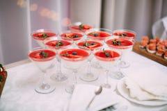 Veel wijnglazen op groene lijst Rode cocktails in glazen klaar voor partijmensen Stock Afbeelding