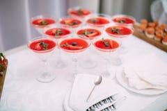 Veel wijnglazen op groene lijst Rode cocktails in glazen klaar voor partijmensen Royalty-vrije Stock Afbeelding