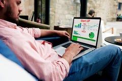 Veelbelovende jonge bankbediende die een statistisch verslag op uw computer maken royalty-vrije stock afbeelding