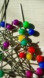 Veelkleurige speld op wit punaise in verschillende kleuren van de knoop wordt geplaatst, willekeurig macroclose-up dat stock foto's