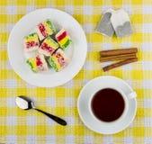 Veelkleurige Turkse verrukking in plaat, kop thee en kaneel Royalty-vrije Stock Fotografie