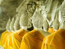 Veelvoud dat de beeldhouwwerken van Boedha met gele robes in c mediteert Stock Foto