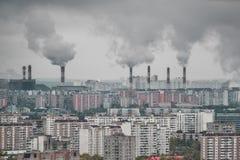 Veelvoudige fabriekspijpen die steenkoolrook produceren in stadsatmosfeer royalty-vrije stock afbeeldingen