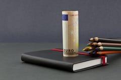 Veelvoudige kleurenpotloden met euro munt en zwart dagboek stock afbeelding