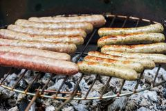 Veelvoudige smakelijke worsten op de grill in dichte omhooggaand stock foto