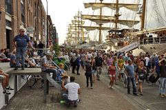 The Veemkade at the time of the Sail Amsterdam. Veemkade, Amsterdam, the Netherlands - August 21, 2015: Spectators walking on the pavement next to the tall ships Royalty Free Stock Photo