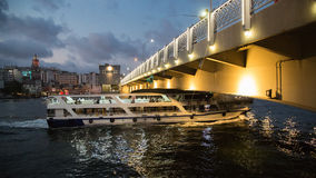 Veerboot die onder de Galata-brug bij nacht overgaan Gouden Hoorn Turkije, Istanboel stock afbeelding
