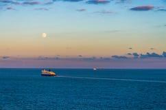 Veerboot en grote schepen op zee onder een volle maan Royalty-vrije Stock Fotografie