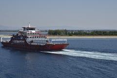 Veerboot op het overzees met Keramoti-strand op achtergrond Stock Foto's