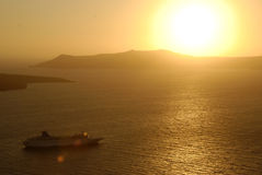 Veerboot tegen Santorini-Zonsondergang wordt gesilhouetteerd die Stock Fotografie