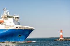 Veerboot voor de haveningang van Warnemà ¼ nde met de rode vuurtoren stock foto's