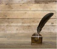 Veerganzepen en glasinktpot op houten stock foto