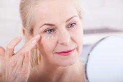 Veertig jaar oude vrouwen die rimpels in spiegel bekijken Plastische chirurgie en collageeninjecties makeup Macrogezicht Selectie royalty-vrije stock foto