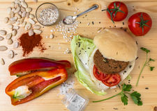 Veg burger. Homemade veg burger with ingredients, on a light wooden background. Top view Stock Images
