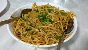 Veg Chinese Noodles. A close up click of a bowl containing veg noodles garnished with green herbs stock photo