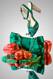 Veg fashion. A close-up of a blue purse, high-heeled shoe, beads and vegetables Stock Images