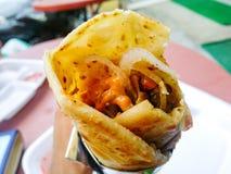 Veg kathi roll. Holding and Eating delicious kathi roll stock photography